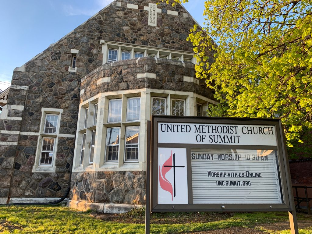 Image of United Methodist Church of Summit, NJ with a sign explaining you can worship with us online by visiting umcsummit.org